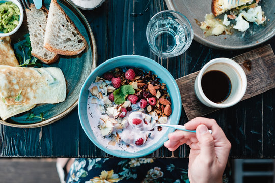 Woman sitting at a breakfast table eating oatmeal with raspberries, nuts and seeds
