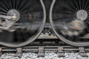 The rotating wheels of steam locomotive on railroad. Detail of steam locomotive wheel on tracks.