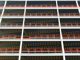 looking upwards view of large modern commercial building under construction with steel beams and girders with orange safety fences