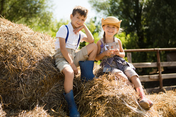 Two little children the brother and a sister is resting on the hayloft on a farm in the summer