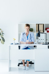 adult female doctor in white coat using smartphone at table in office