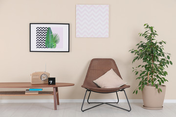 Stylish living room interior with armchair and houseplant near beige wall