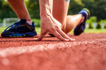 Joint care for runners. Hand of sportsman on running track low start position. Runner ready to go close up. Ultimate remedies. Flexibility is ability to stretch joint to limit of range movement Wall mural