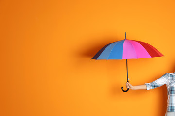 Wall Mural - Woman holding beautiful umbrella on color background with space for design