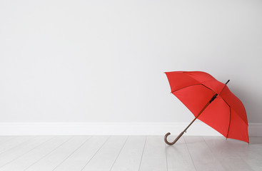 Wall Mural - Beautiful open umbrella on floor near white wall with space for design