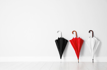 Beautiful bright umbrellas on floor near white wall with space for design