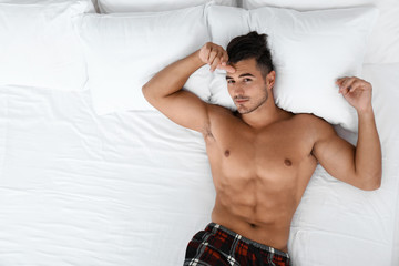 Sexy young man lying on bed with soft pillows at home, top view