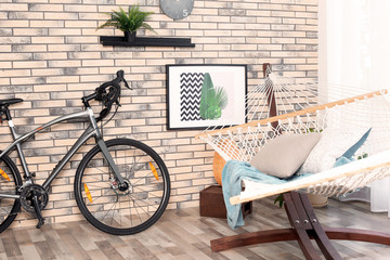 Modern bicycle and hammock in stylish room interior