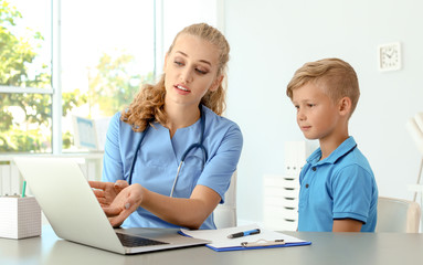 Female medical assistant explaining physical examination result to child in clinic