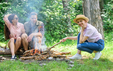Friends hang out near bonfire picnic. Company youth camping forest prepare bonfire for picnic. Add some wood to fire. Company friends or family making bonfire in forest nature background