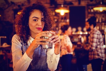Portrait of young woman having a cocktail drink