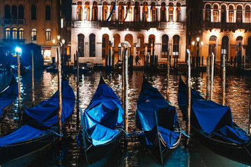 Row of gondolas and glowing streets. Italy, Europe
