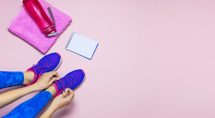 Young woman in sporting blue leggings laces sneakers, preparing for training. Accessories for sports, bottle of water towel notebook on pastel pink background flat lay top view. Fitness concept
