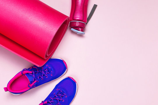 Ultra blue violet pink female sneakers, yoga mat, water bottle on pastel pink background flat lay top view with copy space. Sports shoes, fitness, concept of healthy lifestile, everyday training.