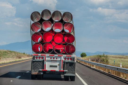 hinter einem LKW mit Rohren am Anhänger nachfahren