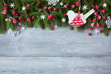 Christmas wooden background with spruce branches, red berries, bird and snowflakes