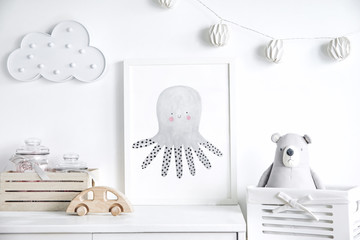 Stylish scandinavian newborn baby shelf with mock up photo frame,  box, teddy bear and toys. Modern interior with white walls and wooden accessories.