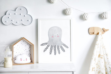 Stylish scandinavian nursery shelf with mock up photo frame, bottle with milk and toys. Modern interior with white walls and wooden accessories.