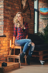 Sensual blonde hipster girl with long curly hair dressed in a fleece shirt and jeans holds a cup of morning coffee sitting on a wooden stool at a studio with a loft interior.