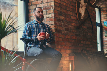 Handsome bearded hipster male in a blue fleece shirt and jeans holds a cup of morning coffee while sitting on a window sill at a studio with a loft interior.