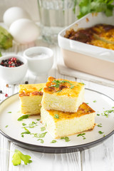 Fluffy omelet baked with zucchini, kids healthy Breakfast, delicious casserole. On white wooden background