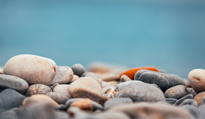 Foto op Plexiglas Stenen in het Zand Close up of pebble and stone rock beach with blue ocean