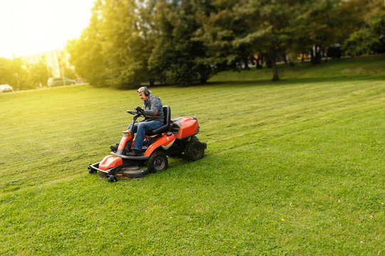 Men riding a lawnmower in a sunny day