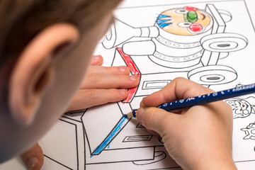 A young boy is coloring a picture of train with blue pencil. Close-up photo taken from above his head seeing only one ear , cheak and hands holding a blue pencil.