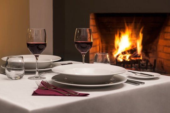 Dinner table for romantic evening, with fireplace in behind.