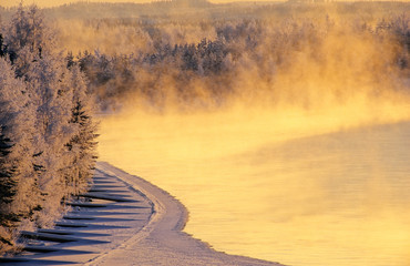 Mist over freezing river on a cold winter day. Winter landscape in Finland.
