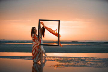 Portrait of a Two Young women holding an empty frame. Girls traveler with wooden picture frame at colorful sea sunset. Summer vacation and travel concept