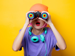 Young style girl in purple clothes with LGBT binoculars on yellow background.  Clothes in 1980s style