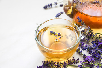 cup of lavender tea and teapot with fresh flowers over white marble table. herbal drink. close up