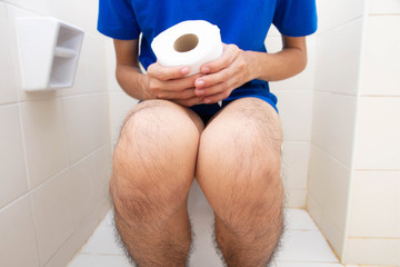 Young man constipated sitting on toilet and hand holding tissue