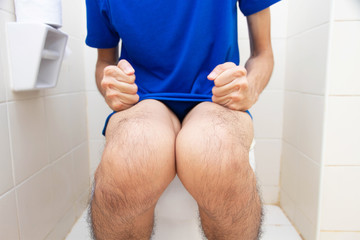 Young man suffering from constipation sitting on toilet