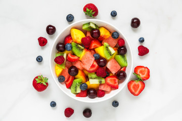 healthy fresh fruit and berry salad in a bowl on white marble background. healthy food