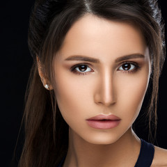 Close up of gorgeous and seductive woman with perfect bronze clean skin, plumps lips, confident looking at camera. Young brunette girl after procedure and makeup in beauty salon. Concept of beauty.