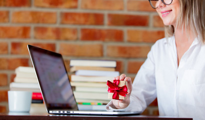 Young businesswoman sitting on a table with laptop computer and books and gift box. Brick wall on background