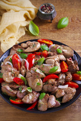 Chicken liver with  tomatoes, onions and basil on black plate, wooden table. vertical