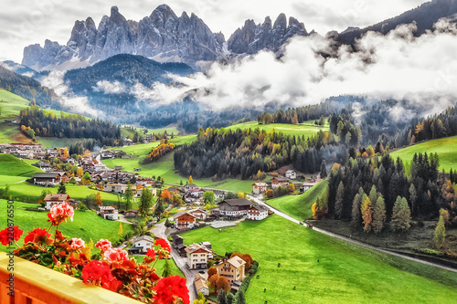 Wall mural Italy, Dolomite mountains. Fascinating Alpine Village - Santa Maddalena, amazing view from balcony of hotel on flowers, green valley, Alps Odle in distance. Landscape photography, travel background.