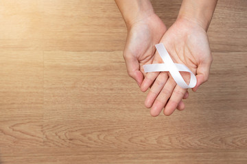 women hands holding white bow, white ribbons on wooden background. Awareness White ribbon for campaign to end violence against women and cancer health care concept