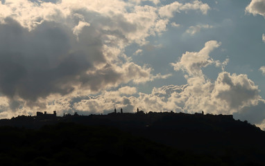 Clouds pass over the silhouette of Tuscan town of Montalcino