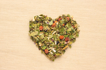 Dried herb leaves heart shaped on jute surface