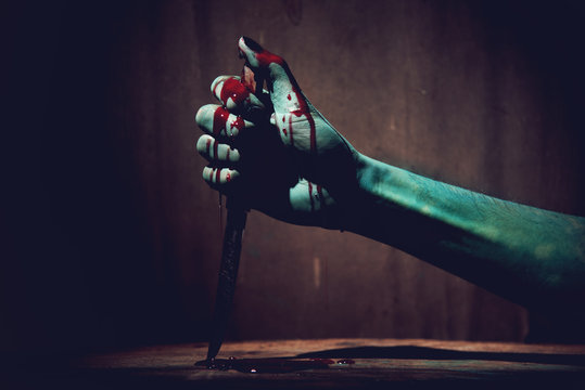 Halloween concept with Bloody stabbing. Hand with knife
