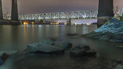 Patullo Bridge, Surrey, British Columbia, Canada. Long exposure of the bridge over the water. Sky Train Bridge.