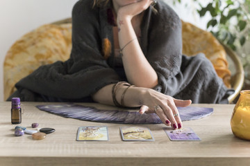 Young redheaded woman reading tarot fortune