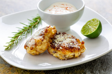 Two shrimp cakes on a white plate with a lemon garlic dipping sauces lemon wedge and a stem or rosemary on a wooden table.