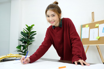 Young asian woman fashion designer working in studio with happiness emotion, small business owner, fashion industry concept
