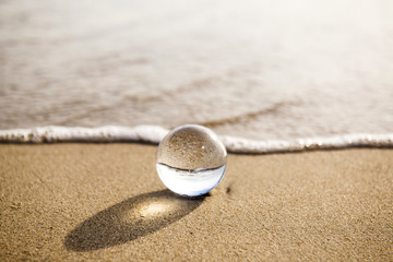 Acrylic Prints Stones in Sand glass ball crystal clear reflecting the sea and beach in the morning