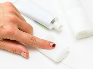 A knife-cut index finger of the left female hand, a tube of ointment and a bandage on a white table.